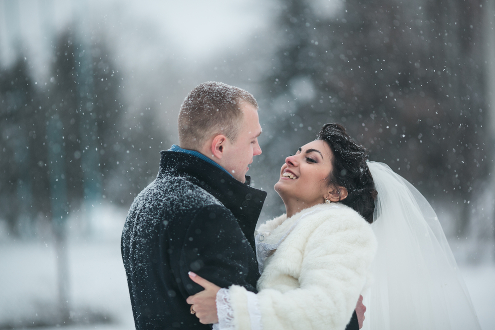 Couple getting married in snowy winter landscape